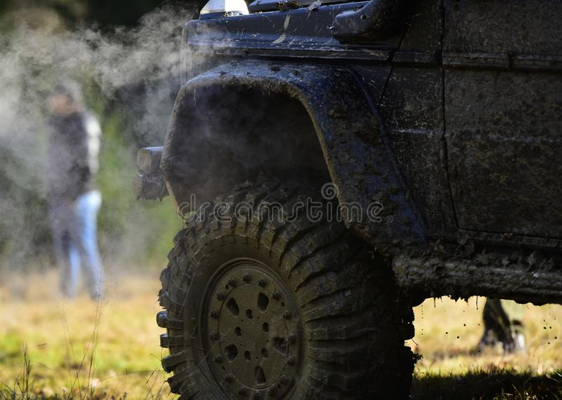 Part of vehicle covered with mud and man near it. SUV on nature background, close up. Side of car covered with dirt and. Cloud of smoke. Off road racing, force stock images