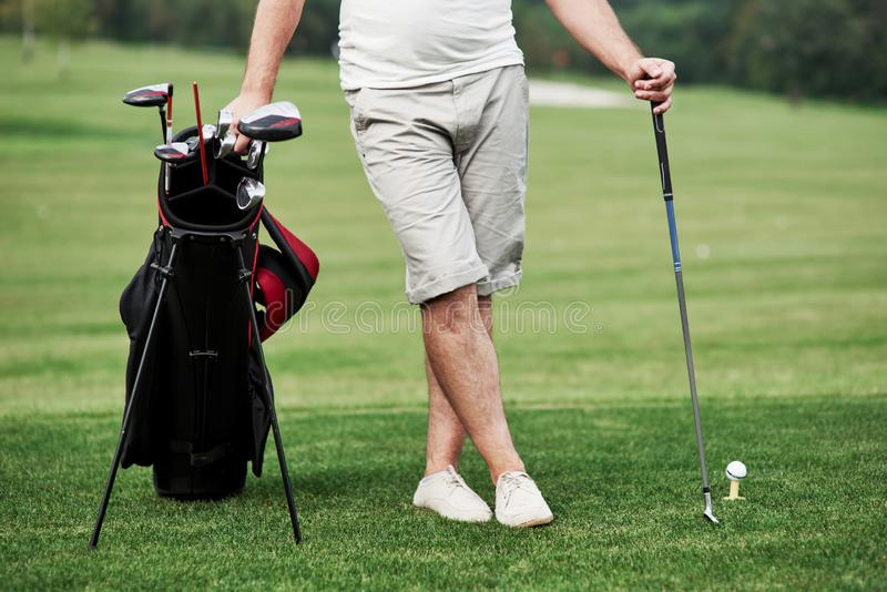 Part view of man standing on the green grass with golf equipment stock photo