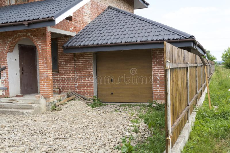 Part view of modern two-storied not finished new brick family cottage house with steep brown shingled roof, attached garage, tempo. Rary wooden fence stock photos