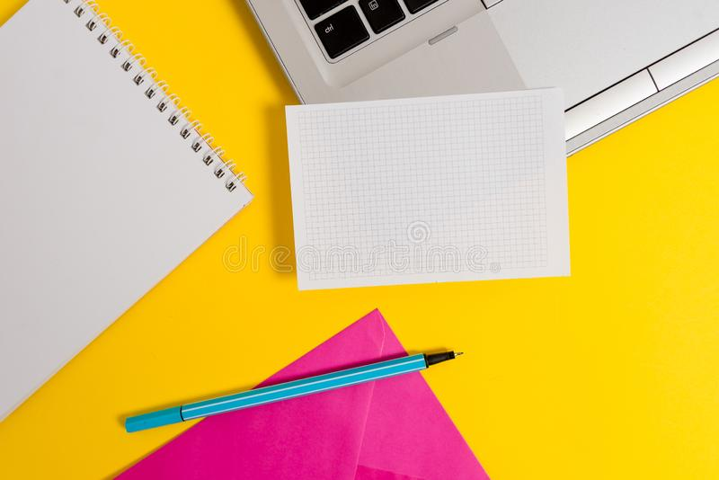 Part view open trendy slim silver metallic laptop highlighter marker squared paper sheet spiral notebook envelope. Laptop marker squared sheet spiral notebook stock photography