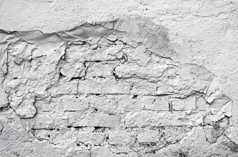 Part of the wall with loose stucco through which brick is visible. White color. stock photography