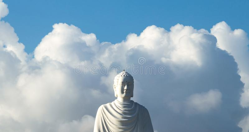 Part of a white Buddha statue on a background of clouds royalty free stock photos