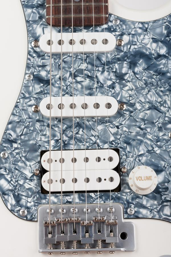 Part of white electric guitar, studio shoot.  2 x Single Coil and 1 x Humbucking. Black Pearl pickguard, Rosewood Fingerboard. Part of white electric guitar royalty free stock photography