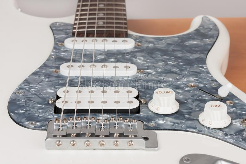 Part of white electric guitar, studio shoot.  2 x Single Coil and 1 x Humbucking. Black Pearl pickguard, Rosewood Fingerboard royalty free stock image