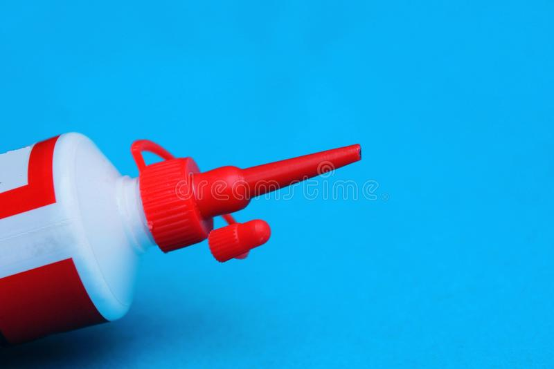 Part of a white plastic tube with a long red cap on a blue background stock image
