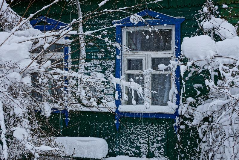 Part of a wooden house with a window and branches of bushes in white snow stock photos