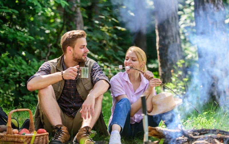 Partagandeavbrott som äter naturbakgrund Förälskad campa skogvandring för par Par sitter nära brasa äter mellanmål och royaltyfria bilder