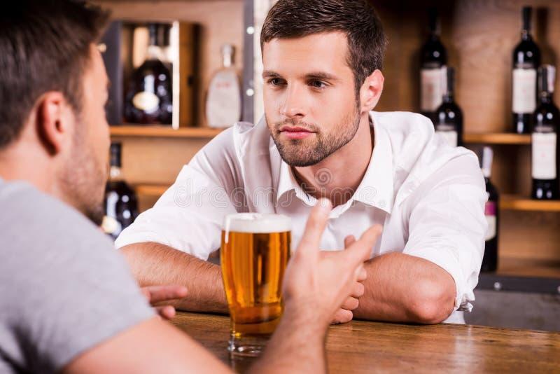 Partager des actualités avec le barman images stock