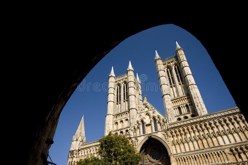 Parte anteriore ad ovest di Lincoln Cathedral veduta da sotto il Ministero delle Finanze Gate, Lincoln, Lincolnshire, Regno Unito fotografie stock libere da diritti