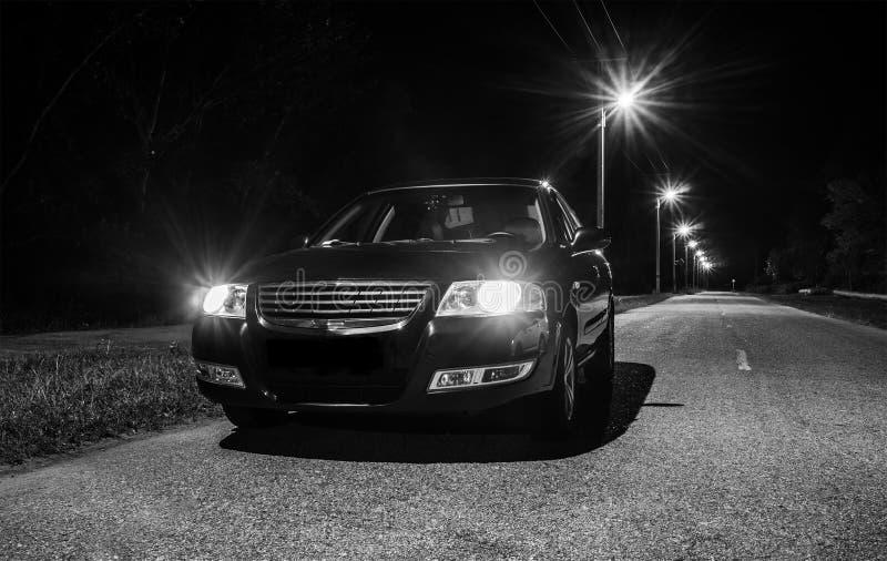 Parte anteriore dell'automobile sulla strada con illuminazione di notte fotografie stock