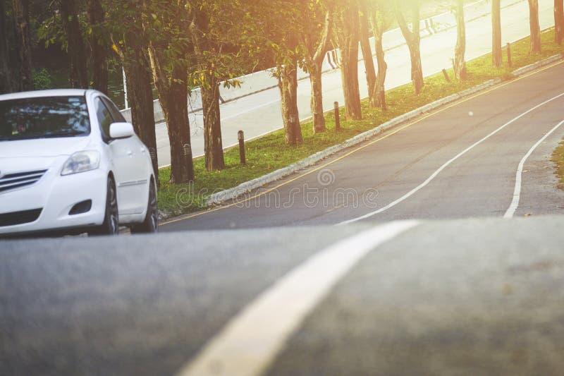 Parte anteriore di nuova automobile bianca che parcheggia sulla strada asfaltata immagine stock libera da diritti