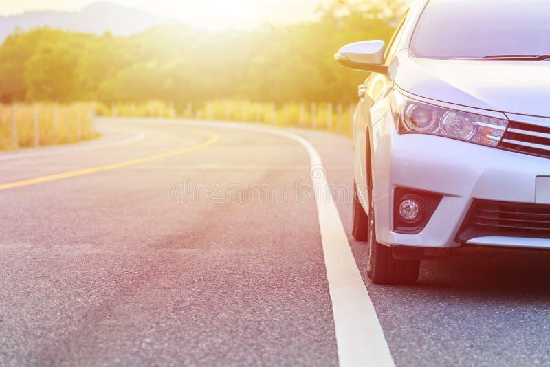 Parte anteriore di nuovo parcheggio d'argento dell'automobile sulla strada asfaltata immagini stock