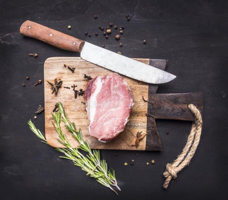 Parte apetitosa de bife cru da carne de porco na placa de corte do vintage com ervas e especiarias para a carne uma faca no backg foto de stock