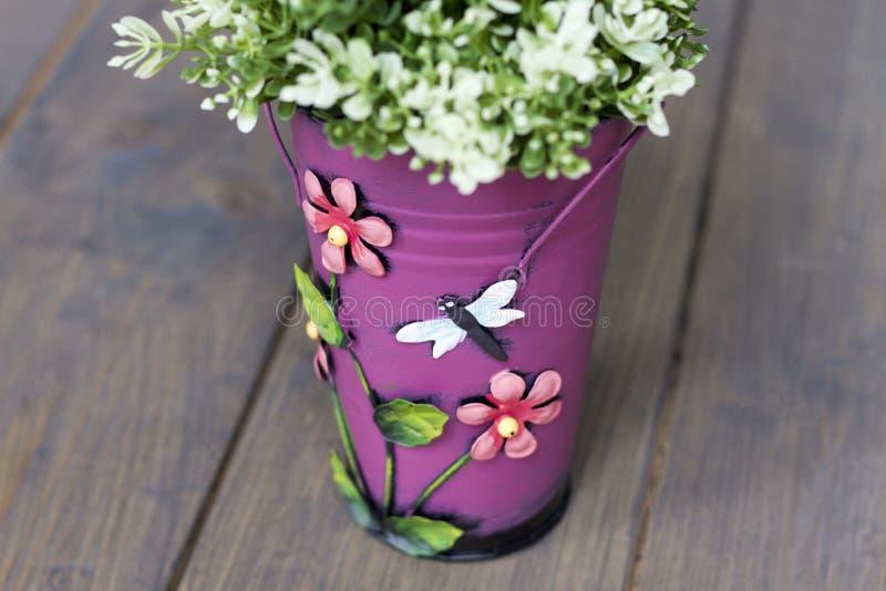 Parte artificiale di un cespuglio verde in un secchio rosa con i fiori e una farfalla su un pavimento di legno immagine stock