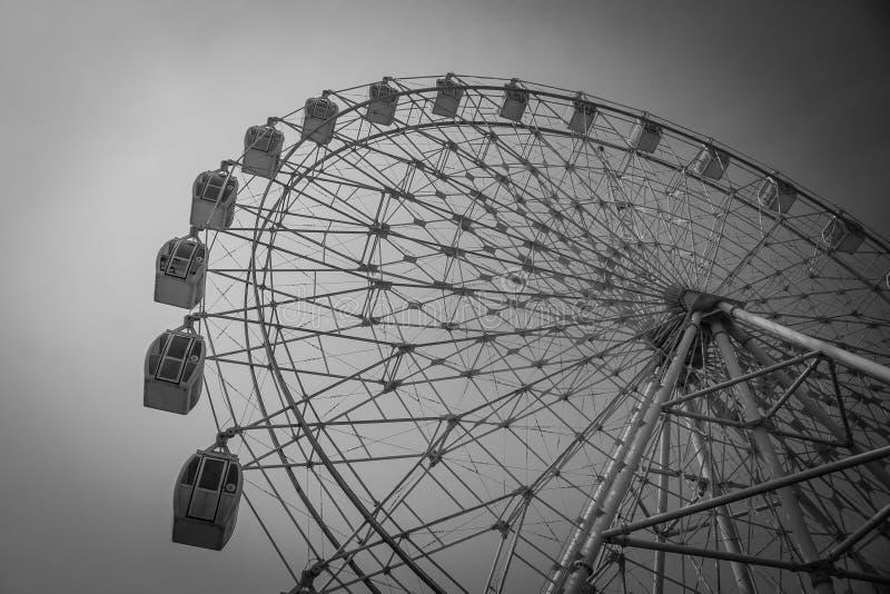 Parte in bianco e nero astratta di immagine della ruota di ferris variopinta con il fondo del cielo blu fotografia stock libera da diritti