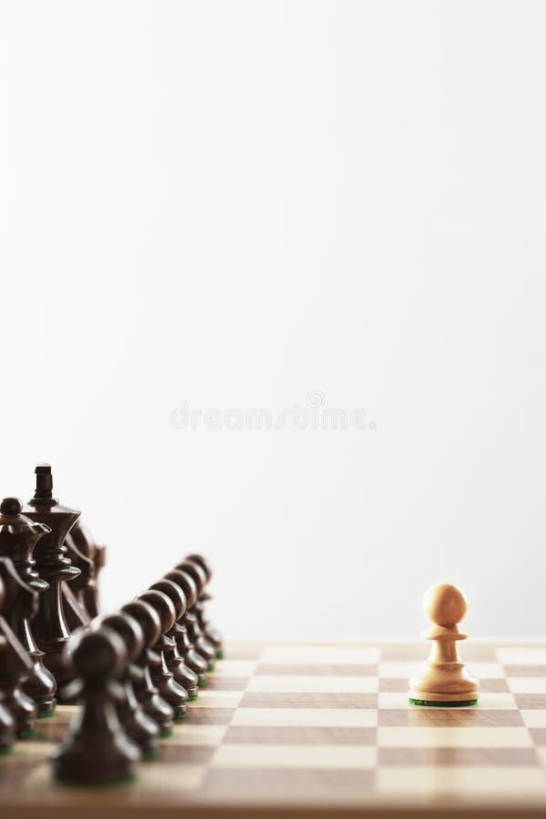 Parte branca do jogo de xadrez única na frente das partes pretas fotografia de stock royalty free