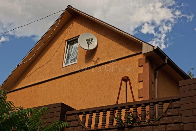 Parte da casa marrom atrás da cerca com uma janela no sótão e uma antena parabólica na parede imagem de stock royalty free