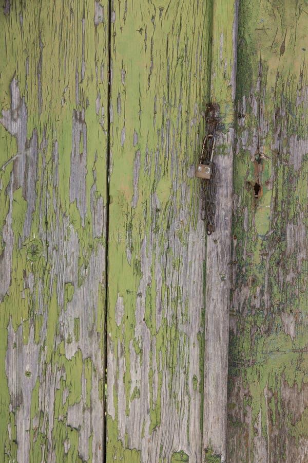 Parte da porta de madeira com descascamento da pintura verde e oxidado muito velhos imagem de stock