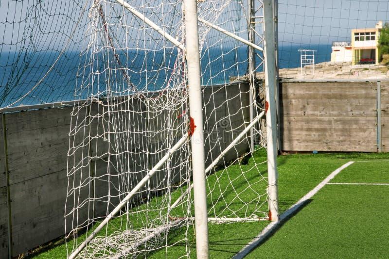Parte da porta do objetivo do futebol com rede branca Feche acima para o objetivo do futebol no campo de futebol com grama verde  foto de stock royalty free