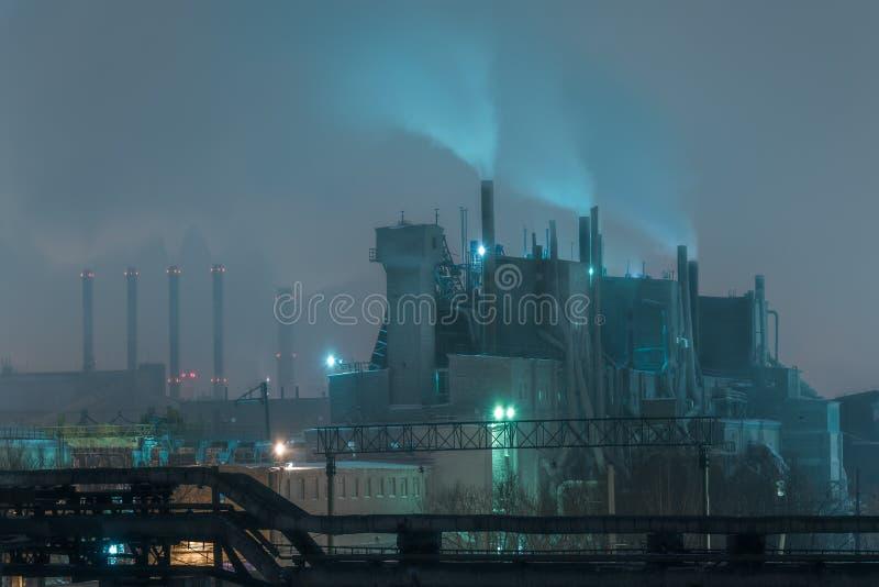 Parte da refinaria de petróleo grande em uma Lua cheia nevoenta imagem de stock