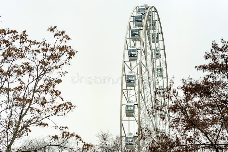 Parte da roda de Ferris branca moderna e do céu cinzento fotografia de stock