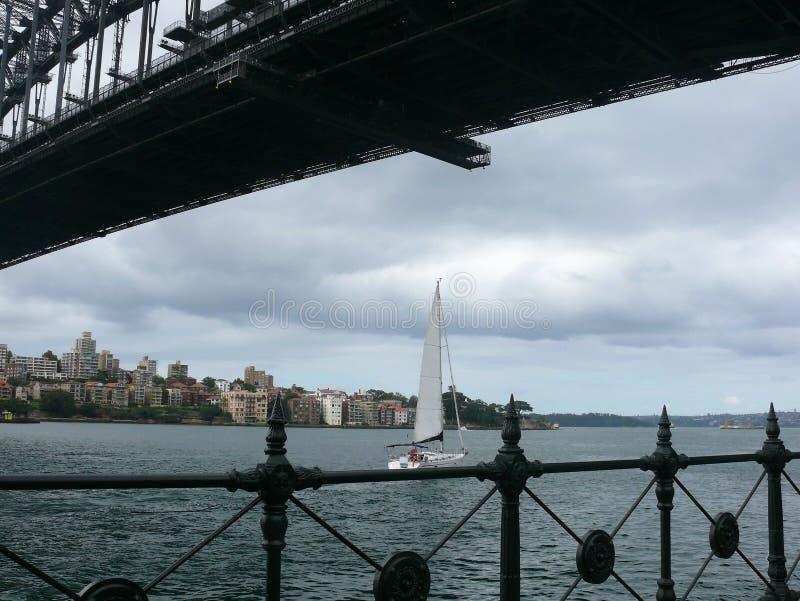 Parte da un ponte d'acciaio prima della riva con le case residenziali ed inferriate e un yacht della navigazione fotografie stock libere da diritti