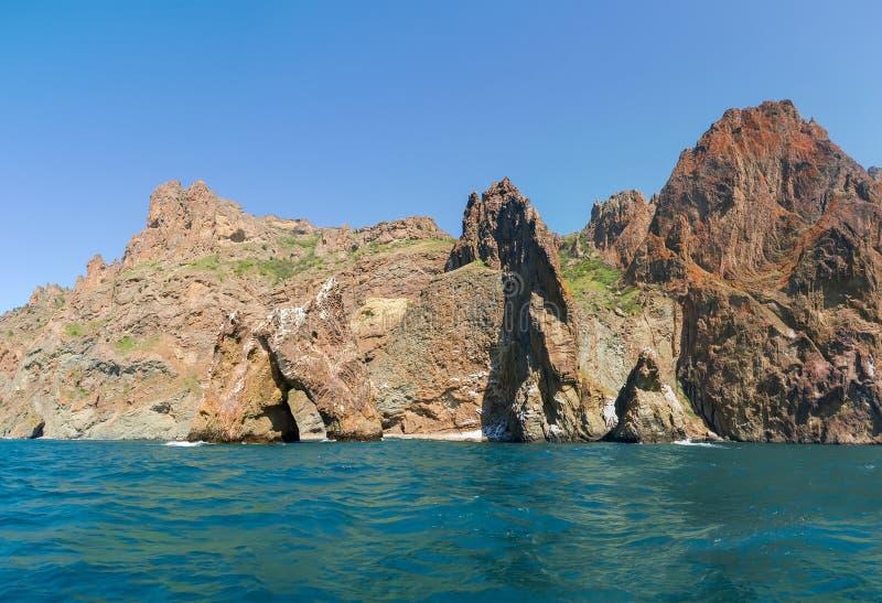 Parte de acantilados costeros del origen volcánico en orilla de mar imágenes de archivo libres de regalías