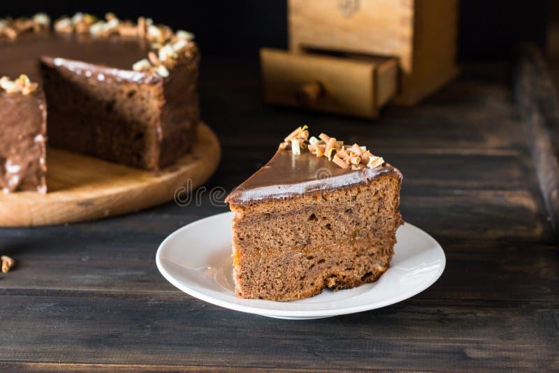 Parte de bolo de chocolate em uma placa branca em de madeira Bolo austríaco tradicional Bolo de Sacher Torta do abricó Conceito d imagens de stock royalty free
