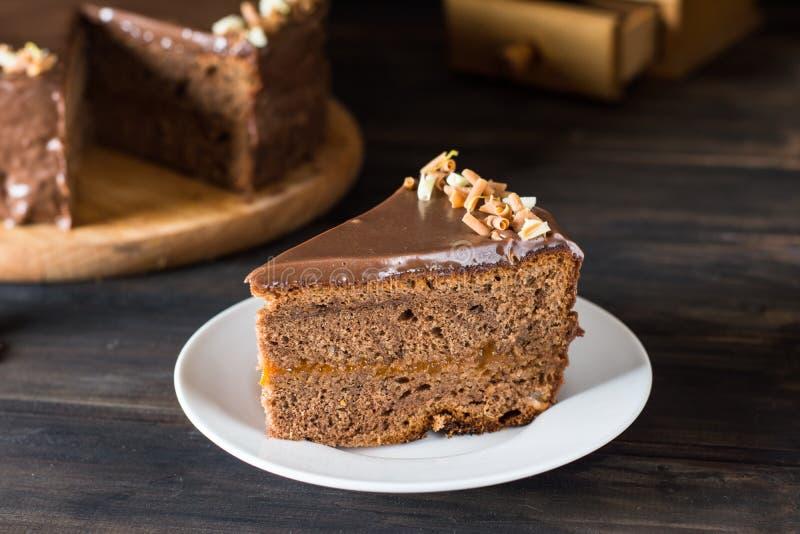 Parte de bolo de chocolate em uma placa branca em de madeira Bolo austríaco tradicional Bolo de Sacher Torta do abricó Conceito d fotos de stock