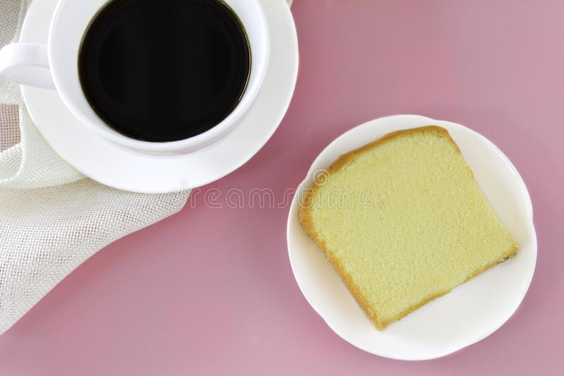 Parte de bolo da manteiga no prato branco servido com o copo do café preto Épocas relaxar o conceito foto de stock