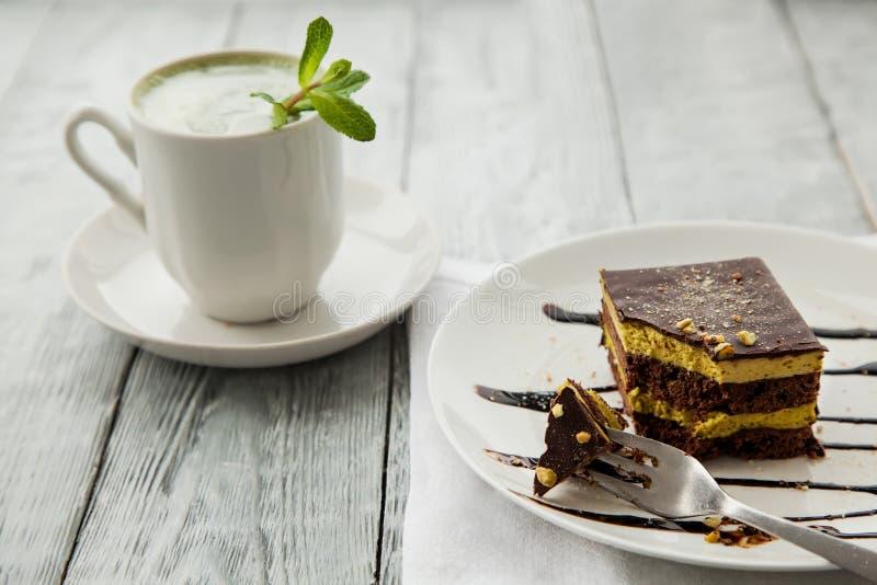Parte de bolo da três-camada e de copo austríacos do chá do matcha em uma placa branca em um café fotos de stock royalty free