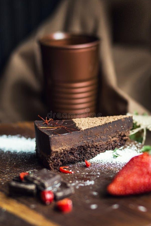 Parte de bolo de chocolate escuro com morango A atmosfera do restaurante ou do café retro vintage imagem de stock royalty free