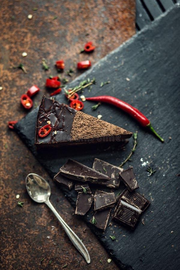 Parte de bolo de chocolate escuro com pimenta encarnado A atmosfera do restaurante ou do café retro vintage foto de stock royalty free