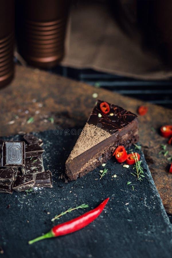 Parte de bolo de chocolate escuro com pimenta encarnado A atmosfera do restaurante ou do café retro vintage fotografia de stock