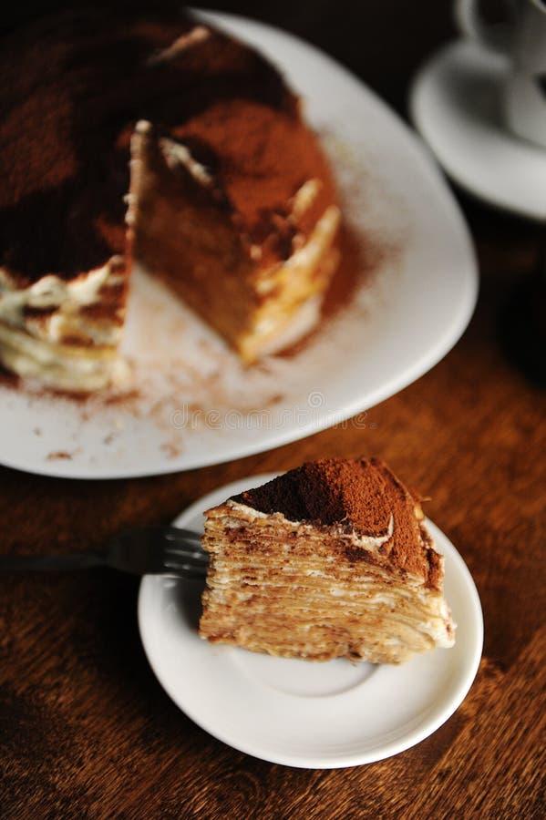 A parte de bolo do crepe com enchimento do tiramisu e cacau pulverulento é servida na placa O interior da cafetaria fotos de stock royalty free