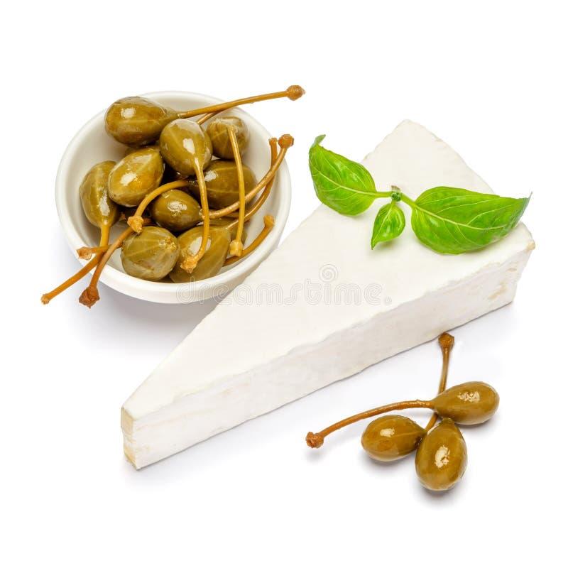 Parte de brie ou queijo e alcaparras do camambert em um fundo branco imagem de stock royalty free