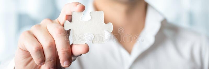 Parte de Holding Jigsaw Puzzle do homem de negócios fotos de stock royalty free