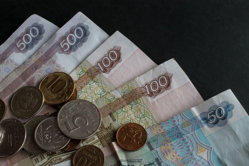 Parte de los billetes rusos y una dispersión de las monedas del metal de diversas denominaciones en ellas primer en un fondo negr imagen de archivo