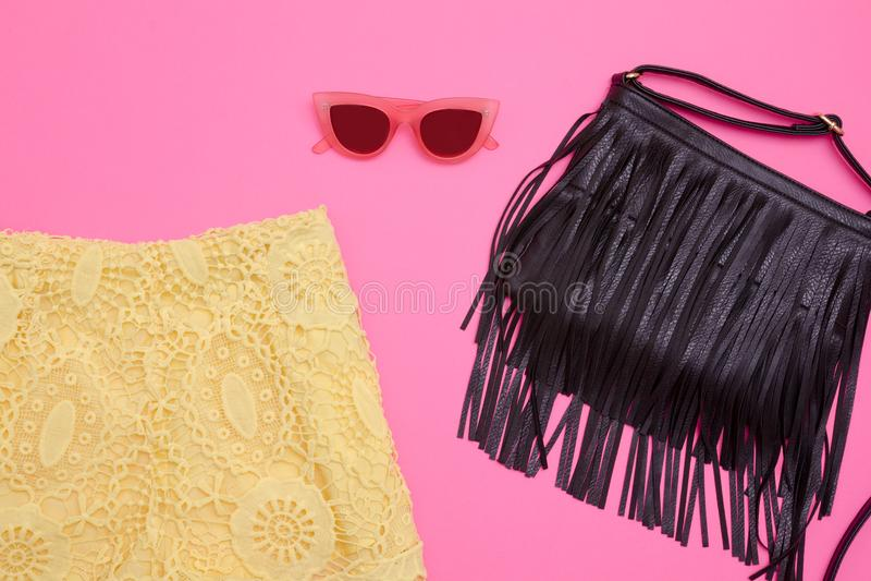 Parte de pantalones cortos amarillos del cordón, un bolso negro con la franja y vidrios rosas Fondo rosado brillante, primer fotos de archivo libres de regalías
