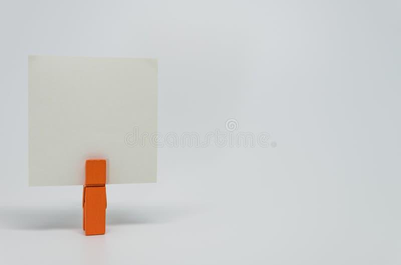 Parte de papel do memorando apertada pelo grampo de madeira alaranjado com fundo branco e foco seletivo foto de stock