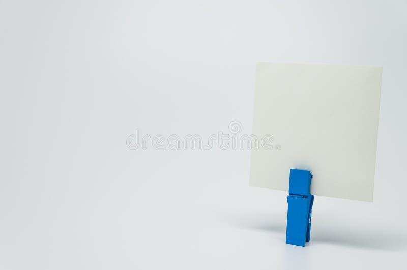 Parte de papel do memorando apertada pelo grampo de madeira azul com fundo branco e foco seletivo foto de stock royalty free