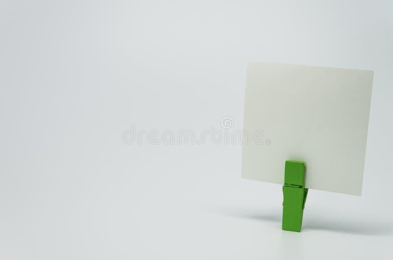 Parte de papel do memorando apertada pelo grampo de madeira verde com fundo branco e foco seletivo fotografia de stock