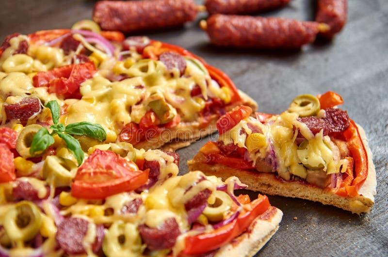 Parte de pizza com salame, tomates, pimenta de sino, cebola, azeitonas verdes, milho, queijo, especiarias No fundo borrado pizza  fotos de stock royalty free