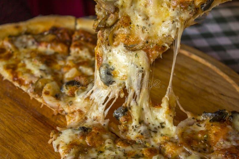 Parte de pizza tomada de uma placa de madeira uma fatia de pizza com queijo quente derretido fotos de stock royalty free