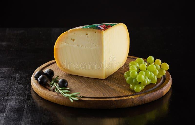 Parte de queijo, de azeitonas pretas e de uvas na placa de madeira foto de stock royalty free