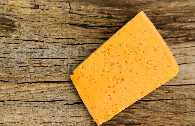 Parte de queijo em um fundo de madeira fotografia de stock royalty free