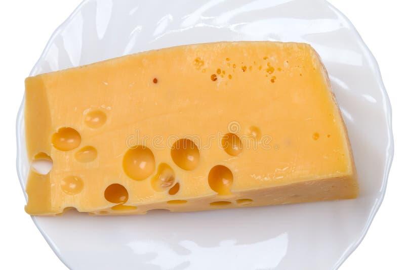 Parte de queijo em uma placa branca fotografia de stock