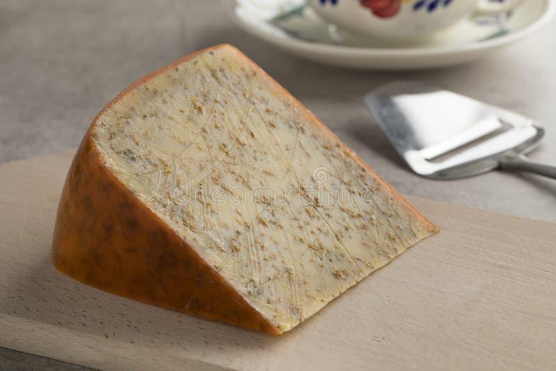 Parte de queijo maduro velho do cominhos fotografia de stock