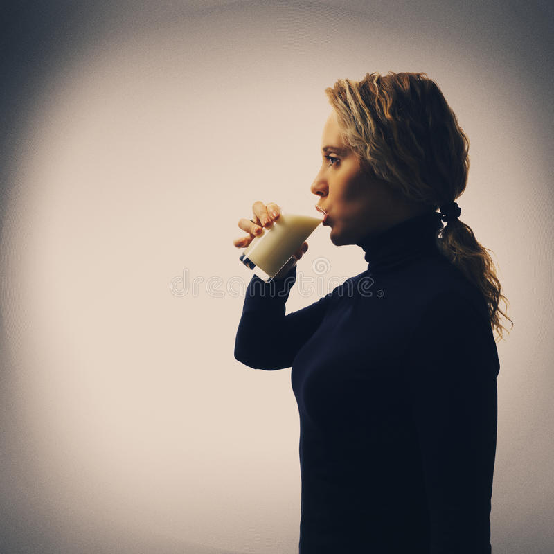 Parte de serie Retrato de la leche de consumo de la mujer joven en vidrio fotos de archivo