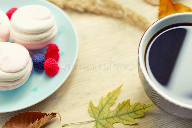 Parte de uma grande xícara de café e de marshmallows em um fundo de madeira com folhas de outono fotografia de stock